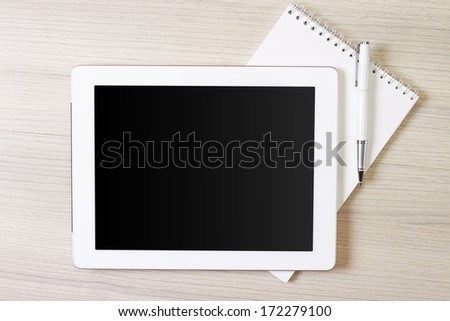digital tablet with notepad and pen on wooden table.  - stock photo