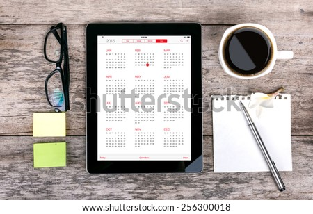 digital tabletdigital tablet as a calendar  and coffee cup wit  on wooden table and coffee cup on wooden table