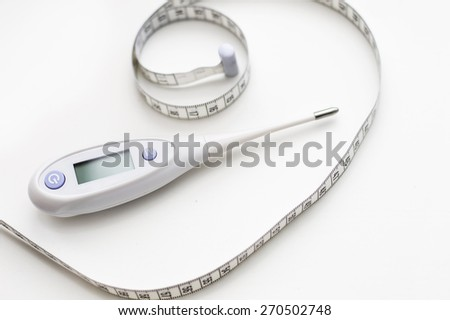 Digital Thermometer and tape measure on a white background - stock photo