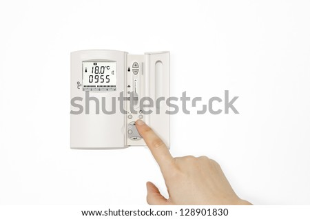 Digital Thermostat. Digital Thermostat with a female hand. Adjusting and setting thermostat to save energy