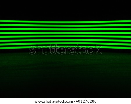 Digitally generated image of green light line over black background on black wooden table - stock photo