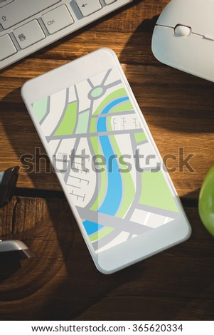 Digitally generated image of map against smartphone on desk