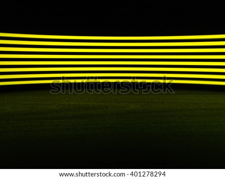 Digitally generated image of yellow light line over black background on black wooden table - stock photo