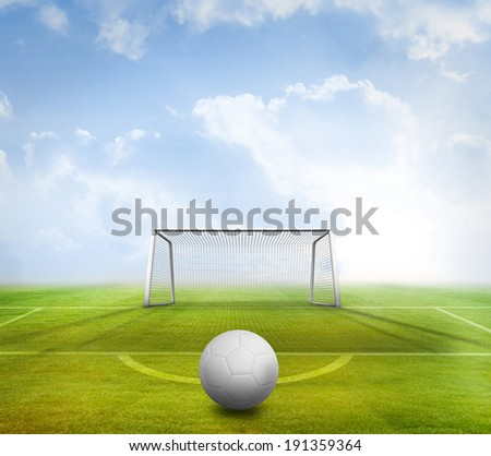 Digitally generated white leather football against football pitch and goal under blue sky - stock photo