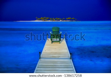 Digitally manipulated image of an adirondack chair sitting on a dock with a ocean island in the background. - stock photo