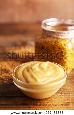 Dijon Mustard in glass jar and mustard sauce in glass bowl on wooden background - stock photo