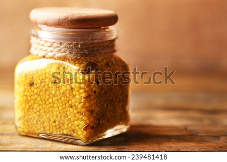 Dijon Mustard in glass jar on wooden background - stock photo
