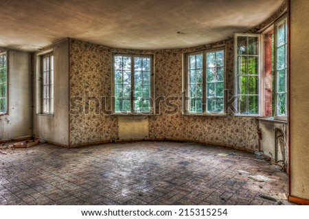 Dilapidated living room in an abandoned house, HDR - stock photo