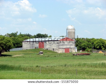 dilapidated old building large barn and silo - stock photo