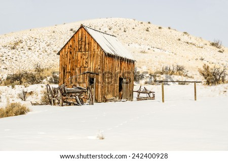 Dilapidated wagon, an outhouse, and a barn surrounded by fresh snow on a winter day - stock photo