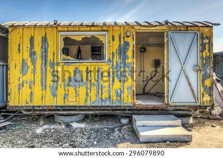Dilapidated yellow work site hut - stock photo