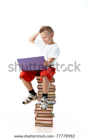Diligent preschooler sitting on the top of book heap with laptop