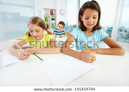 Diligent pupils being busy doing their schoolwork - stock photo