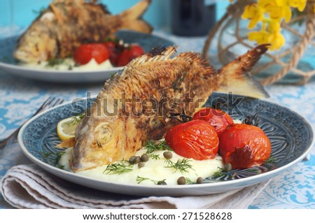 dill and lemon bream fish with creamy mash potato, roasted sweet tomatoes and baby capers on a plate. selective focus - stock photo
