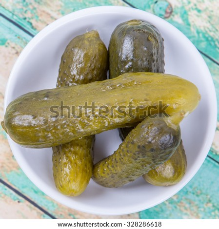 Dill pickles in a white bowl over wooden background