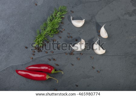 Dill, red peppers, black pepper corn and garlic on a grey slate plate, stock picture