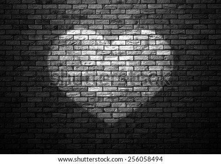 dimly lit old brick wall enlightened cone of light in the shape of heart - stock photo
