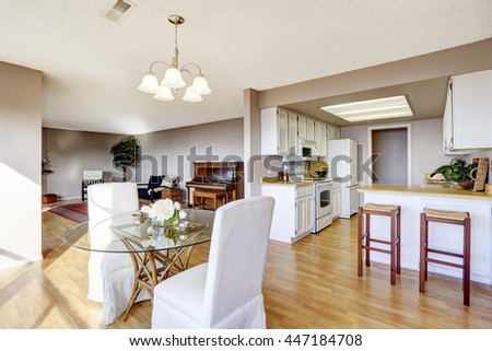 Dining area connected to kitchen and living room with hardwood floor - stock photo