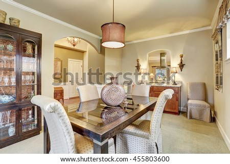 Dining area with beige walls and old wooden furniture. Also carpet floor