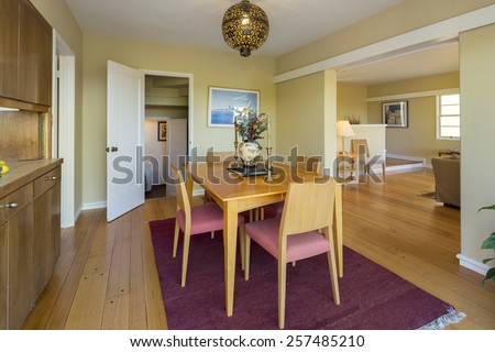 Dining area with wooden table adjacent doors leading to bay view outdoor patio.  - stock photo
