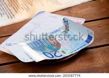 Dining check with Euro banknotes on wooden table. - stock photo