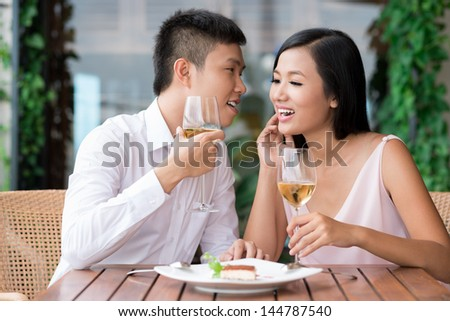Dining couple being excited about the secret they share - stock photo