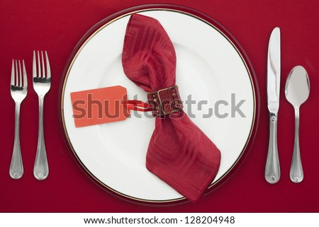 Dining Etiquette with silverware, ceramic plate and place card on a napkin - stock photo