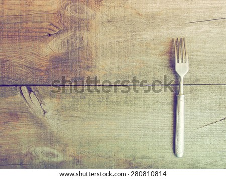 Dining fork on raw wooden background. Grunge style. - stock photo