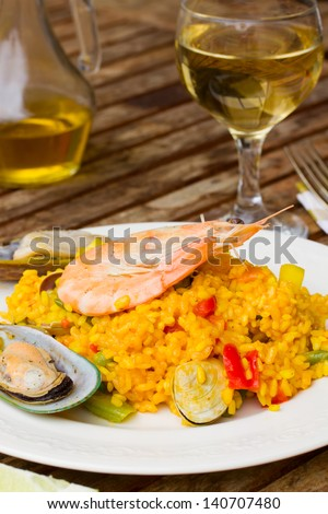 Dining  -  plate with paella and glass of wine - stock photo