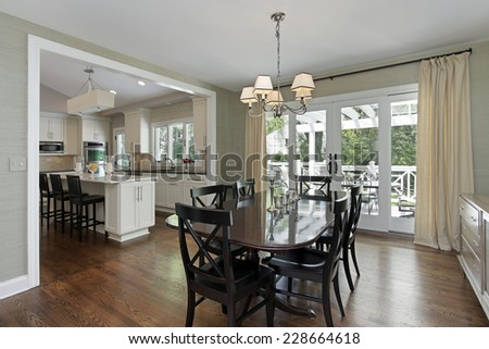 Dining room in luxury home with kitchen view - stock photo