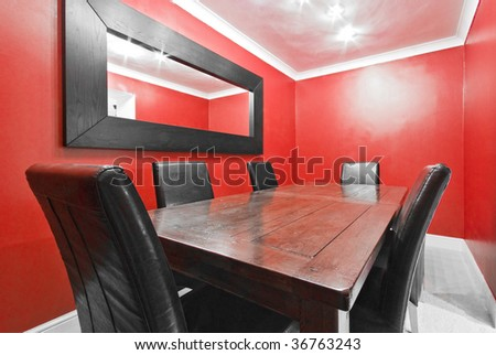 dining room in red with massive wooden table and leather seats