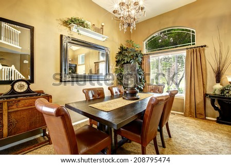 Dining room interior with wooden table and leather chairs - stock photo
