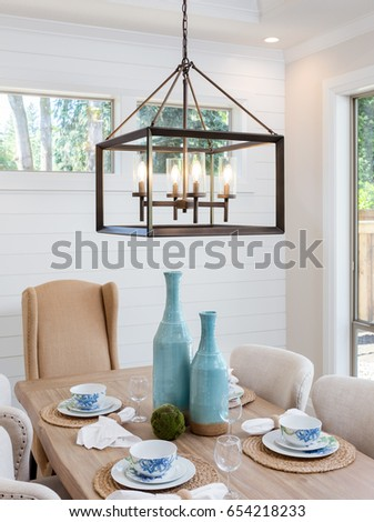 Dining Room Table and Pendant Light Fixture in New Luxury Home. Table is Set with Napkins, Bowls, Plates, and Wine Glasses