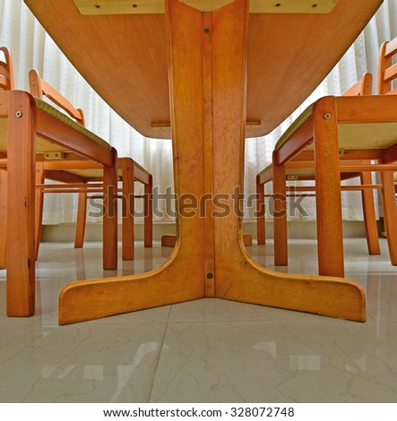Dining room. The underside of a wooden dining table and chairs.