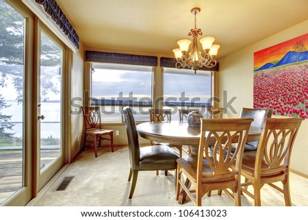 Dining room with beige walls, art and water view.