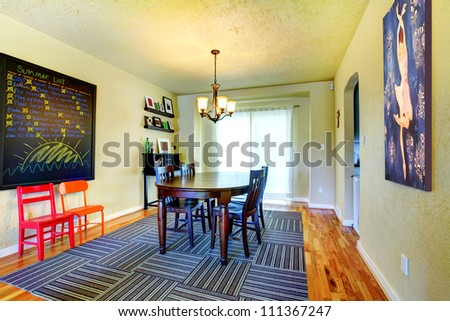 Dining room with black table and grey rug with green walls.