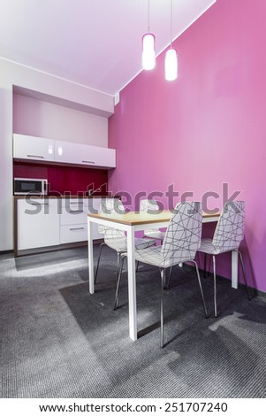 Dining room with kitchenette painted in pink - stock photo