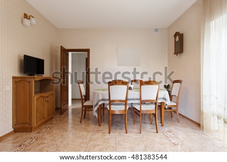 Dining room with wooden table and chairs in mansion