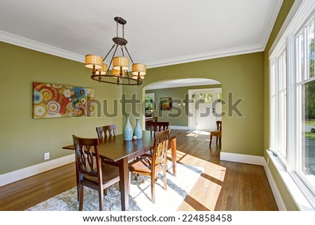 Dining room with wooden table set and rug on the hardwood floor. Room with green walls and white trim - stock photo