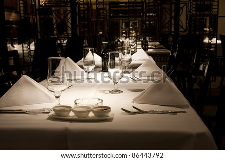 dining setup with wine glasses silver cutlery  and white napkins in a modern restaurant - stock photo