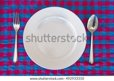 dining table,empty plate knife and fork on the table