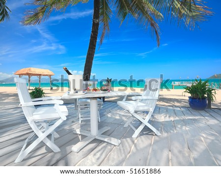 Dining table on the beach close to the ocean - stock photo