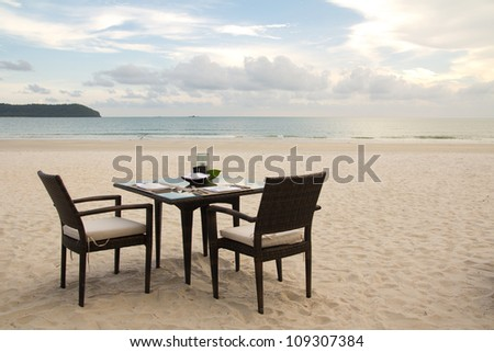 Dining table prepared for two on white sand beach close to ocean - stock photo