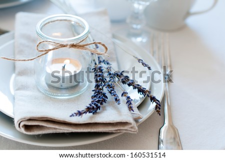 Dining table setting at Provence style, with candles, lavender, vintage crockery and cutlery, closeup. - stock photo