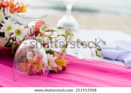 Dining table setting with flowers, and glasses, closeup, outdoor wedding table setup - stock photo