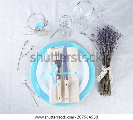 Dining table setting with lavender flowers on light tablecloth background - stock photo