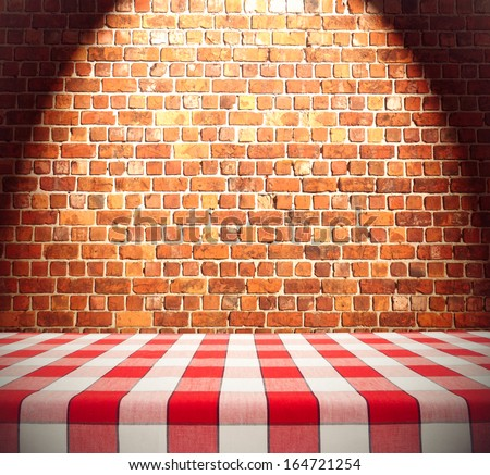 Dining table template on brick wall with spotlight - stock photo