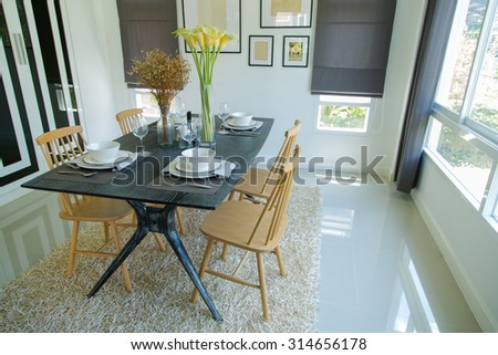 Dining table with set in modern home, Wooden table in Dining room, Luxury corner in the family. - stock photo