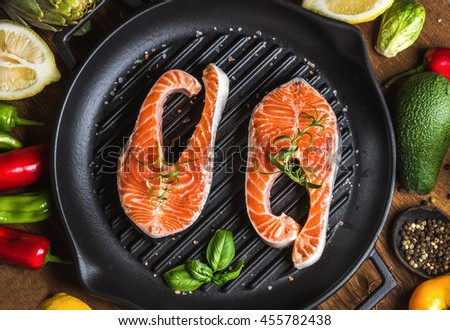 Dinner cooking ingredients. Two pieces of raw uncooked salmon with vegetables, herbs, lemon, avocado, artichokes, spices in iron grilling pan over wooden background, top view, horizontal composition - stock photo