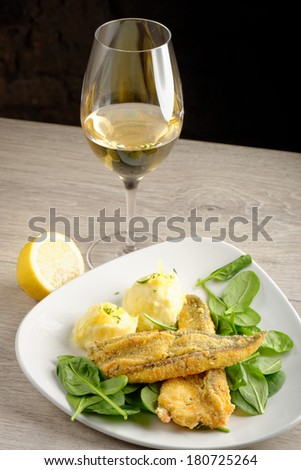 Dinner, Fish fillet with potato, young spinach and white wine  - stock photo